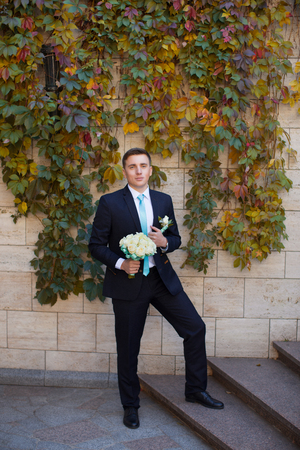 Happy bridegroom in a stylish suit against a brick wall background