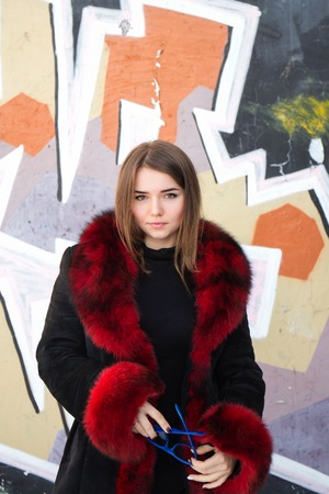 Girl in a black coat with red fur collar.