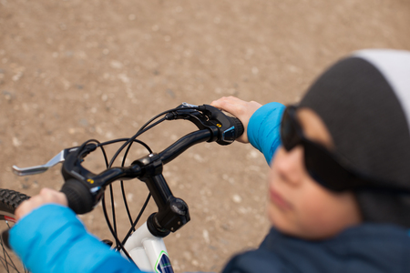 A boy in a blue jacket holds a bicycle handlebars.