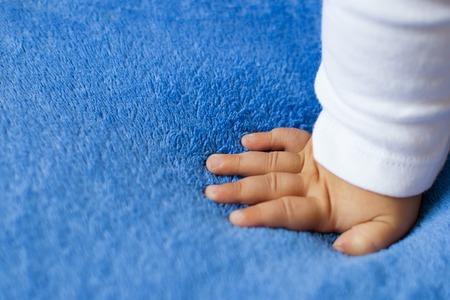 Child's hand on a blue veil