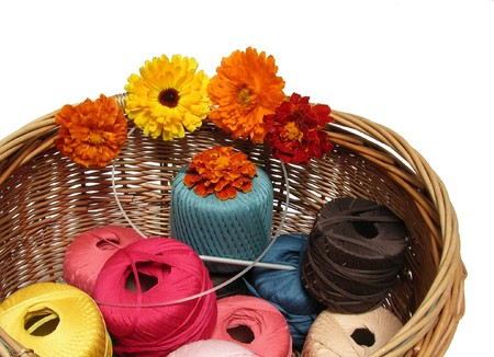 basketful: A basketful of multi-coloured woolen yarn and flowers Stock Photo
