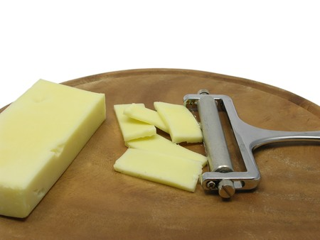 slicer: Hard cheese on wooden plate with cheese slicer Stock Photo