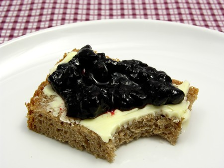 Bitten into a wholemeal butterbread  with bilberry jam placed on a round plate arranged on a placemat photo