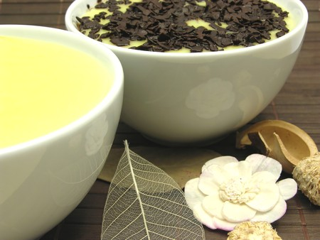Custards with and without grated chocolate in bowls of china ware photo