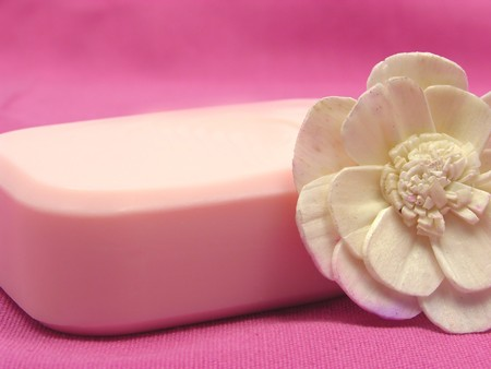 Pink soap with decoration articles on a  pink background photo