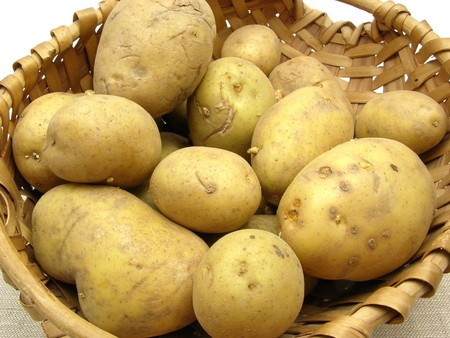 A basket with potatoes on a beige placemat Stock Photo
