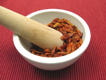 Pestling dried red hot chili pepper in a bowl of chinaware photo