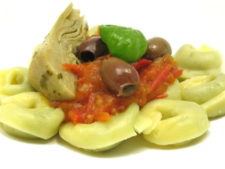 Tortellini  with tomato sauce, leaf of basil, olives and artichoke photo