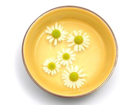 chamomilla: Camomile blooms swim in the water of a  ceramic bowl Stock Photo