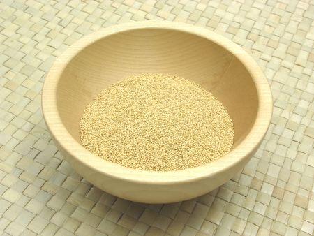 underlay: Wooden bowl with amaranth on rattan underlay Stock Photo
