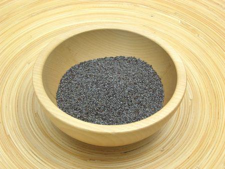 underlay: Bol de madera con semillas de amapola en placa de bamb�