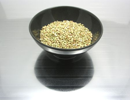 underlay: Black bowl of chinaware with buckwheat on reflecting surface