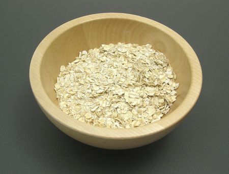 underlay: Wooden bowl with oat flakes on a dull matting