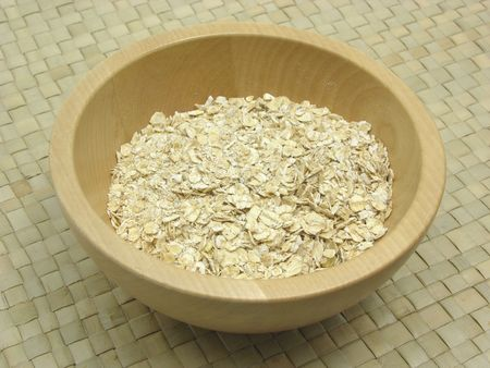 underlay: Wooden bowl with oat flakes on rattan underlay