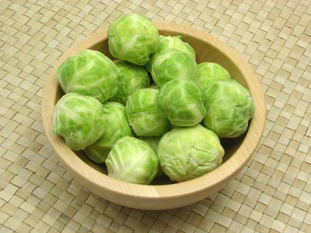 underlay: Wooden bowl with brussels sprouts on rattan underlay