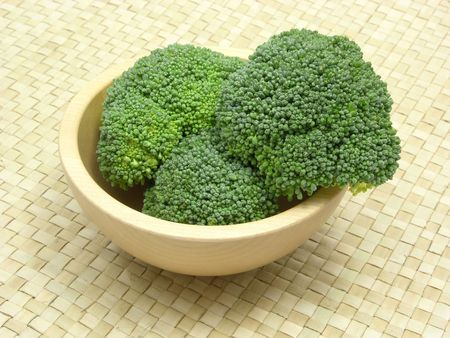 underlay: Wooden bowl with broccoli on rattan underlay Stock Photo