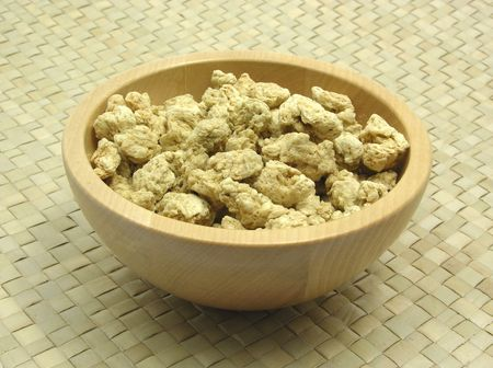 underlay: Wooden bowl with soy granules on rattan underlay