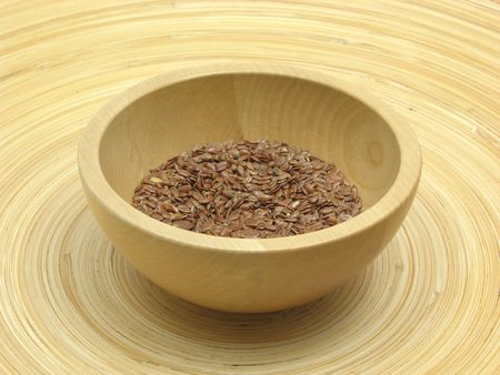 underlay: Wooden bowl with flaxseed on bamboo plate