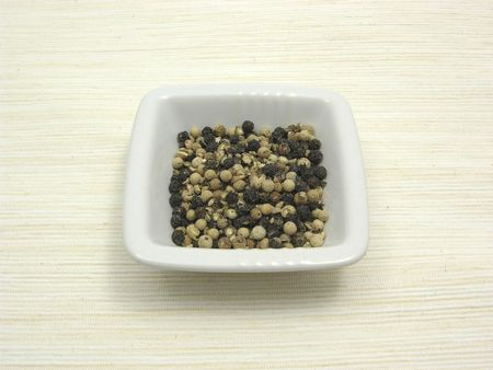 underlay: Bowl of chinaware with peppercorns on beige underlay
