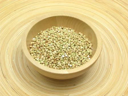 underlay: Wooden bowl with buckwheat on bamboo plate Stock Photo