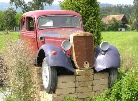 jacked: Rusted veteran car jacked up in the open countryside