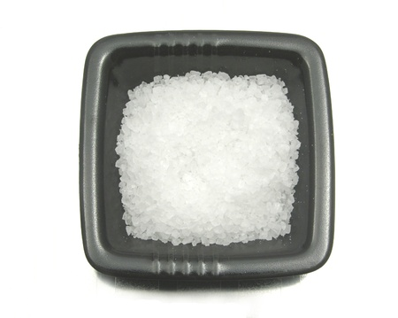 underlay: Black bowl of chinaware with salt on reflecting surface Stock Photo