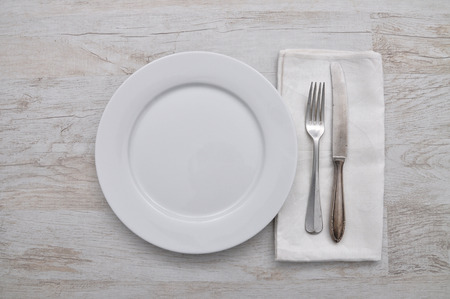 tarnished: Plate, cutlery and cloth on wood Stock Photo