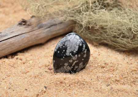 quarz: Snowflake obsidian on beach Stock Photo