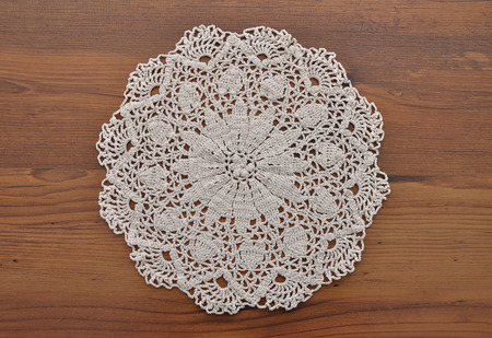 lace doily: Lace doily on dark wood