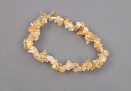 splintered: Splintered rutile quartz chain on gray background Stock Photo