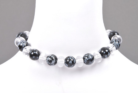 Rock crystal and snowflake obsidian chain on bust Stock Photo