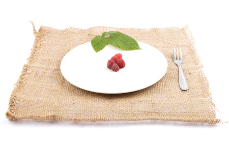 Red raspberries on plate and jute