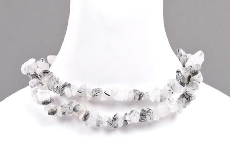 Splintered tourmaline quartz chain on bust Stock Photo