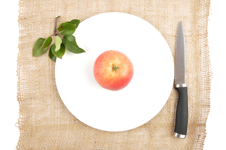 Apple with knife and leaves on jute 스톡 콘텐츠