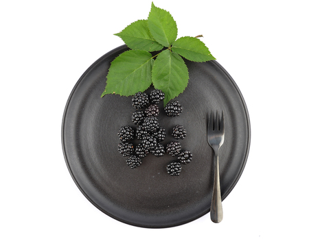 Blackberries on plate and white