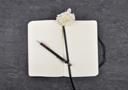 Notebook, pen and white rose on slate