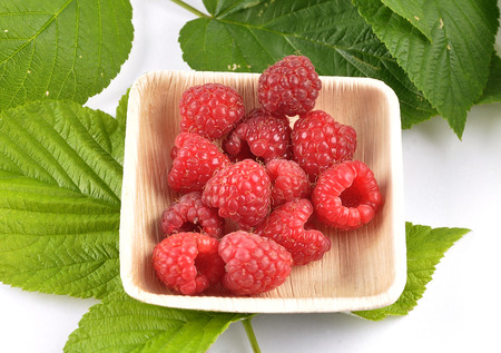 Red raspberries with leaves in bowl