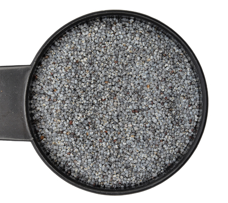 Poppy seeds in measuring spoon on white background