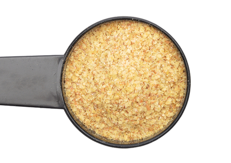 Wheat germs in measuring spoon on white background