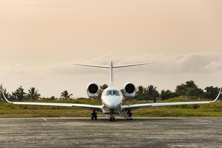 プライベート ジェットは、熱帯の島に滑走路に座っています。