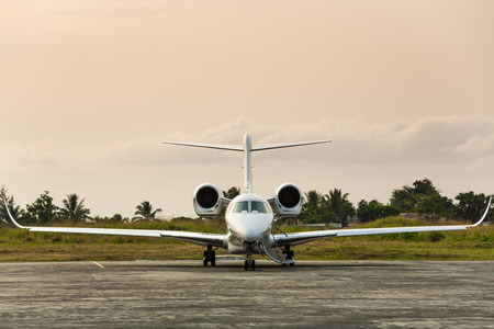 Private jet sits on the runway on a tropical island