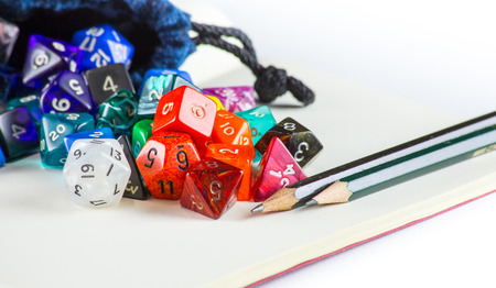 heap of role: Multicolored dice spilling out of a Dice bag with Pencils and a notebook Stock Photo