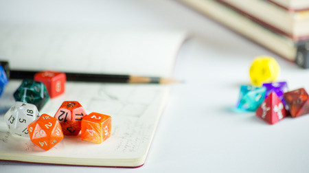 heap of role: Multicolored dice with Pencils, notebook, and books in background