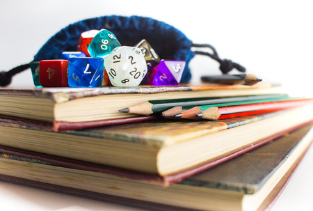 roleplaying: Close up of multicolored Dice with dice bag and Pencils on top of three Books