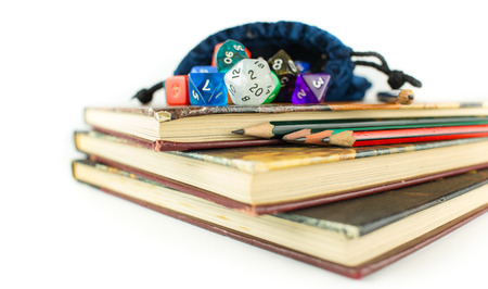 heap of role: Multicolored dice with dice bag and Pencils on top of three Books