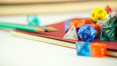 heap of role: Close up of multicolored dice with Pencils on a red Notebook
