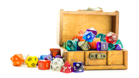 A small wooden chest overflows with multicolored dice