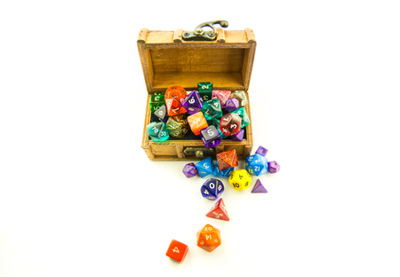 heap of role: Top down shot of a small wooden chest overflowing with multicolored dice