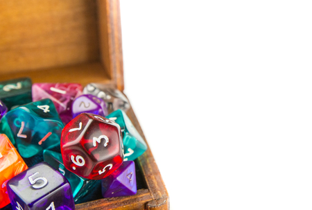 heap of role: Close up of a small wooden chest full of multicolored dice