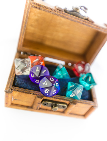 roleplaying: Top down shot of a small wooden chest containing multicolored dice set